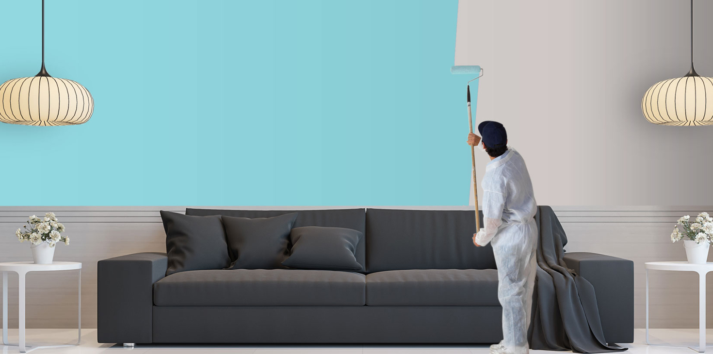 sterling painting services worker painting a living rome from white walls to turquoise.